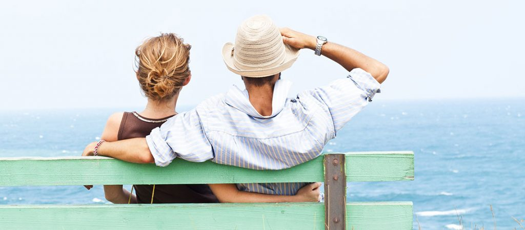 Couple sitting on bench at beach