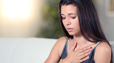 Young woman breathing deeply with hand on heart
