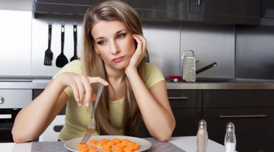 Woman deject over a plate of carrots