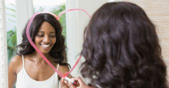 Woman drawing heart on mirror