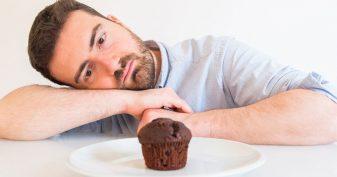 Man looking longingly at cupcake