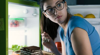young woman sneaking cake from fridge